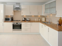 Clean and simple kitchen with white units topped with a wood effect worktop